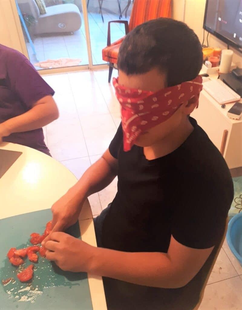 אחד הילדים חותך עגבניה (בעזרת סכין חד פעמית) כשעיניו מכוסות