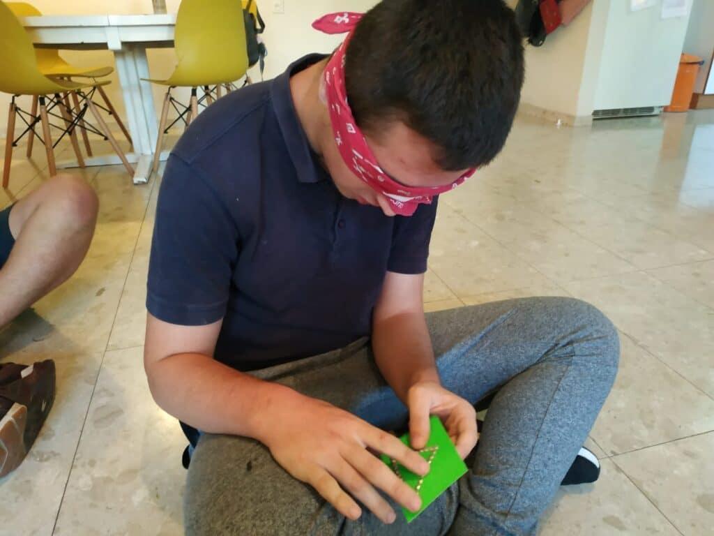 אחת הילדים עם עיניים מכוסות מנסה למשש בריסטול שעליו נקודות בולטות היוצרות צורת משולש